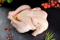 Rohes Fleisch Ungekochtes Geflügel des ganzen Huhns im schwarzen Steinhintergrund stockfotografie