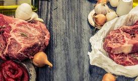 Rohes frisches gemarmortes Fleisch im Papier mit Öl und Gewürzen auf rustikalem hölzernem Hintergrund, Fahne für Website mit dem  Lizenzfreies Stockbild