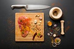 Rohes frisches Schweinefleisch an Bord mit Würzen auf dunklem Hintergrund Stockfoto