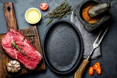 Rohes FrischfleischsteakRindsfilet, Kräuter und Gewürze um Bratpfannenplatte Lebensmittel, das ackground mit Kopienraum kocht Lizenzfreies Stockbild