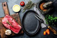 Rohes FrischfleischsteakRindsfilet, Kräuter und Gewürze um Bratpfannenplatte Lebensmittel, das ackground mit Kopienraum kocht Stockbilder