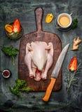 Rohes ganzes Huhn auf altem Schneidebrett mit Bestandteilen für geschmackvolles Kochen und Küchenmesser Stockfoto
