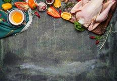 Rohes ganzes Huhn mit Öl- und Gemüsebestandteilen für das geschmackvolle Kochen auf rustikalem Hintergrund, Draufsicht, Grenze Lizenzfreies Stockfoto