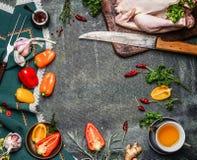 Rohes ganzes Huhn mit Öl- und Gemüsebestandteilen für das Kochen auf rustikalem Hintergrund, Rahmen, Draufsicht Stockbilder