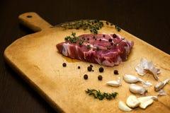 Rohes gemarmortes Rindfleisch auf einem Schneidebrett Auf einem schwarzen Hintergrund Stockfoto