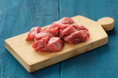 Rohes mageres Fleisch schneidet auf hölzernes Brett auf tiefem blauem Hintergrund lizenzfreies stockfoto