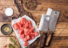 Rohes mageres gewürfeltes Kasserollenrindfleisch-Schweinefleischsteak auf hackendem Brett mit Weinlesefleischbeilen auf hölzernem lizenzfreie stockbilder