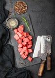 Rohes mageres gew?rfeltes Kasserollenrindfleisch-Schweinefleischsteak auf hackendem Brett mit Weinlesefleischbeilen auf Steinhint stockbild