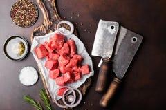 Rohes mageres gew?rfeltes Kasserollenrindfleisch-Schweinefleischsteak auf hackendem Brett mit Weinlesefleischbeilen auf braunem H stockfotos