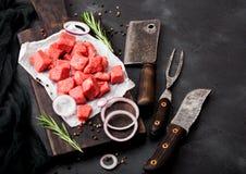 Rohes mageres gew?rfeltes Kasserollenrindfleisch-Schweinefleischsteak mit Weinlesefleischbeil und Gabel mit Messer auf Steinhinte stockfoto
