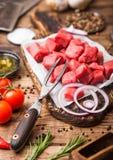 Rohes mageres gew?rfeltes Kasserollenrindfleisch-Schweinefleischsteak mit Weinlesefleischbeil und -messer und Gabel auf h?lzernem lizenzfreie stockbilder