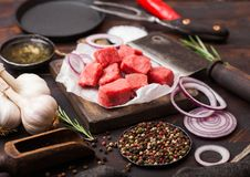 Rohes mageres gew?rfeltes Kasserollenrindfleisch-Schweinefleischsteak mit Weinlesefleischbeil und -messer und Gabel auf h?lzernem stockfoto