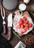 Rohes mageres gew?rfeltes Kasserollenrindfleisch-Schweinefleischsteak mit Weinlesefleischbeil und -messer und Gabel auf h?lzernem stockbilder