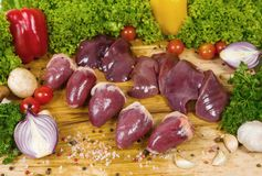 Rohes Nieren-, Leber- und Kaninchenherz auf einer Schnittholzoberfläche mit Kirschtomaten, Kopfsalat, Knoblauch, Paprika, Rosmari lizenzfreies stockfoto
