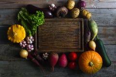 Rohes organisches Frischgemüse und hölzernes Brett in der rustikalen Art Erntezeit, buntes Gemüse, gesunder Lebensstil Stockfotografie