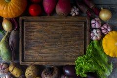 Rohes organisches Frischgemüse und hölzernes Brett in der rustikalen Art Erntezeit, buntes Gemüse, gesunder Lebensstil Lizenzfreies Stockfoto