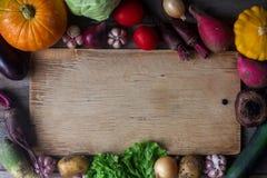 Rohes organisches Frischgemüse und hölzernes Brett in der rustikalen Art Erntezeit, buntes Gemüse, gesunder Lebensstil Lizenzfreies Stockbild