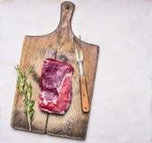 Rohes ribeye Steak auf einem Schneidebrett mit einer Weinlesefleischgabel und ein Zweig des Rosmarins auf weißem hölzernem rustik Stockfotografie