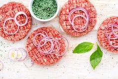 Rohes Rinderhackfleischfleischkotelett für das Kochen von Burgern mit Zwiebelringen und -gewürzen auf weißem hölzernem Hintergrun lizenzfreie stockfotografie