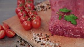 Rohes Rindfleisch auf einem hölzernen Hintergrund mit Gewürzen und Tomaten stock video footage