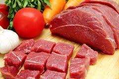 Rohes Rindfleisch mit Gemüse auf hölzerner Platte Stockfotografie