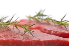 Rohes Rindfleisch mit mit dem Zweig des Rosmarins Stockfotos