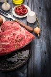Rohes Rindfleischfleisch in der schwarzen Wanne mit Gewürzen und in der Soße auf blauem Holztisch, Vorbereitung Lizenzfreie Stockfotos