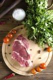 Rohes Rindfleischsteak auf einem hölzernen Brett auf einem hölzernen Hintergrund stockfoto