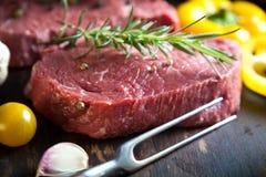 Rohes Rindfleischsteak auf einer dunklen hölzernen Tabelle stockfotografie