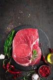 Rohes Rindfleischsteak auf schwarzem Hintergrund mit dem Kochen von Bestandteilen Frisches Rindfleischfleisch stockfotos