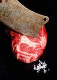 Rohes Rindfleischsteak mit Fleischbeil auf Draufsicht des dunklen rustikalen Hintergrundes Stockfotografie