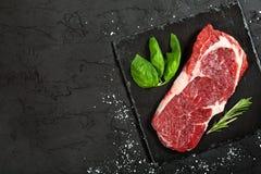 Rohes Rindfleischsteak mit Rosmarin und Pfeffern auf einem dunklen Stein Stockfotografie