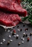 Rohes Rindfleischsteak mit Rosmarinniederlassungen auf Pergamentpapier mit Pfeffer und Salz stockfotografie