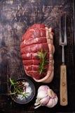 Rohes Roastbeefhinterteil, -gewürze und -fleisch gabelt auf dunklem Metall-backgroun Stockfotografie