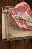 Rohes Schulterlamm auf hölzernem Brett und Tabelle Stockfotos
