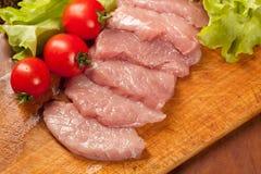 Rohes Schweinefleisch Ð ¾ n das hölzerne Brett Tomate und lettice stockfotografie