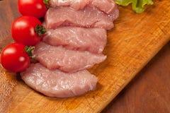 Rohes Schweinefleisch Ð ¾ n das hölzerne Brett Tomate und lettice lizenzfreies stockfoto