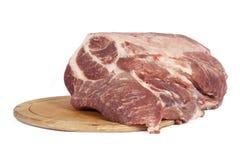 Rohes Schweinefleisch auf einem runden Brett Lizenzfreie Stockbilder