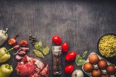 Rohes Schweinefleisch auf einer dunklen Holzoberfläche und Bestandteilen für das Kochen Nahrungsmittelhintergrund mit Exemplar-Pl Stockfotos