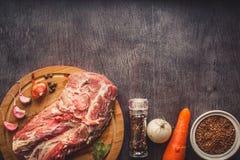 Rohes Schweinefleisch auf einer dunklen Holzoberfläche und Bestandteilen für das Kochen Nahrungsmittelhintergrund mit Exemplar-Pl lizenzfreies stockbild