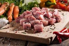 Rohes Schweinefleisch auf Schneidebrett und Frischgemüse Stockfotos