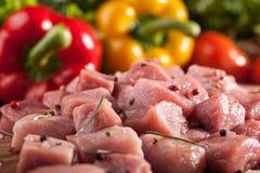 Rohes Schweinefleisch auf Schneidebrett und Frischgemüse schließt oben Stockfoto