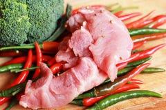 Rohes Schweinefleisch auf Schneidebrett und Gemüse Stockbilder