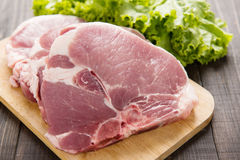 Rohes Schweinefleisch auf Schneidebrett und Gemüse auf hölzernem Hintergrund Lizenzfreie Stockbilder