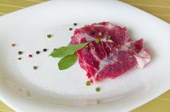 Rohes Schweinefleisch mit Lorbeerblatt, Bälle des Pfeffers auf der weißen Platte, die auf hölzernem Hintergrund liegt Stockbilder