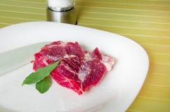 Rohes Schweinefleisch mit Lorbeerblatt, Bälle des Pfeffers auf der weißen Platte, die auf hölzernem Hintergrund liegt Stockfotos