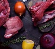 Rohes Schweinefleisch- und Rindfleischfleisch und Rippen auf den dunklen Brettern umgeben durch Zwiebel, Rosmarin und Gewürze lizenzfreies stockbild
