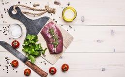 Rohes Schweinefleischsteak mit Rosmarin, Messer für Fleisch, Kirschtomaten und Petersiliengrenze, Platz für hölzerne rustikale Hi Lizenzfreie Stockfotos