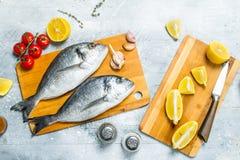 Rohes Seefisch dorado mit Tomaten, Zitronenkeilen und Gewürzen stockfotos