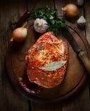 Rohes Stück Schweinefleisch, Zwiebel, Pfeffer, Knoblauch, frische Kräuter auf dem hölzernen Hintergrund Stockfotos